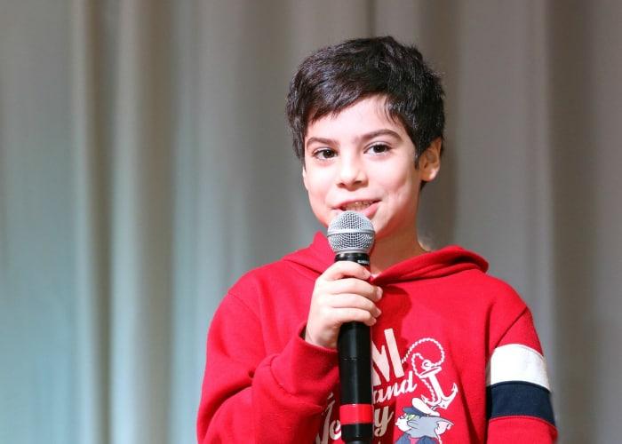Niño con micrófono dando una charla